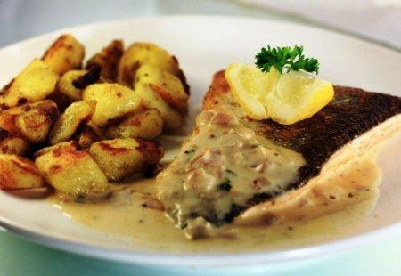 Форель, запечена з картоплею під часниковим соусом